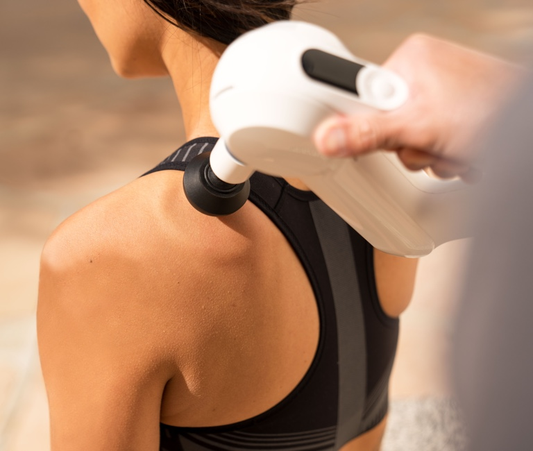 Woman treating shoulder with device