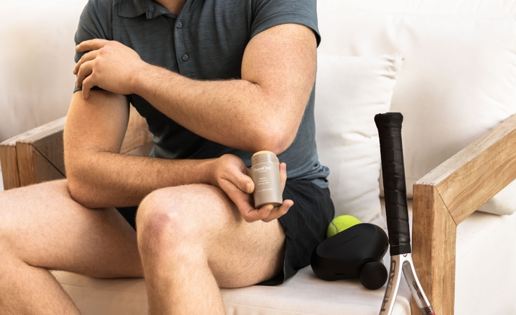 man rubbing perform product on elbow