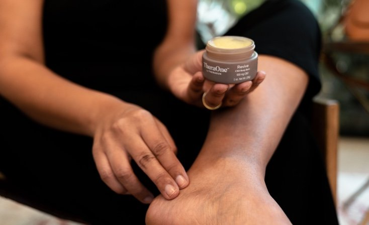 woman rubbing revive cream into ankle