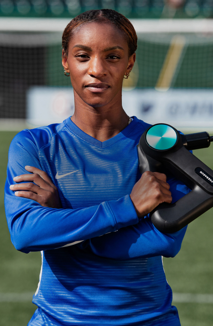 Crystal Dunn posing with Theragun PRO device