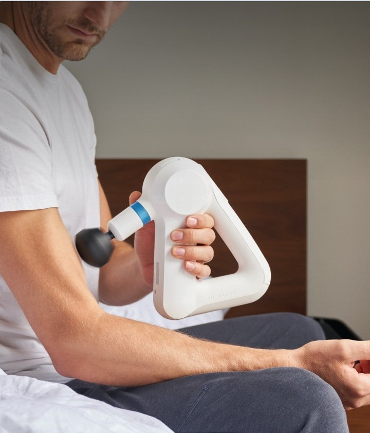 Man treating upper arm with device