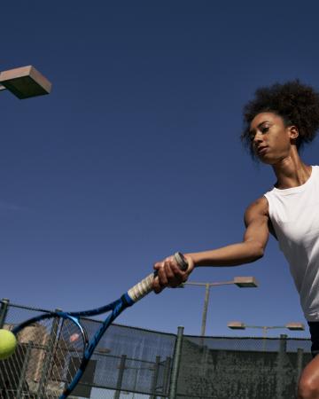 woman hitting tennis ball