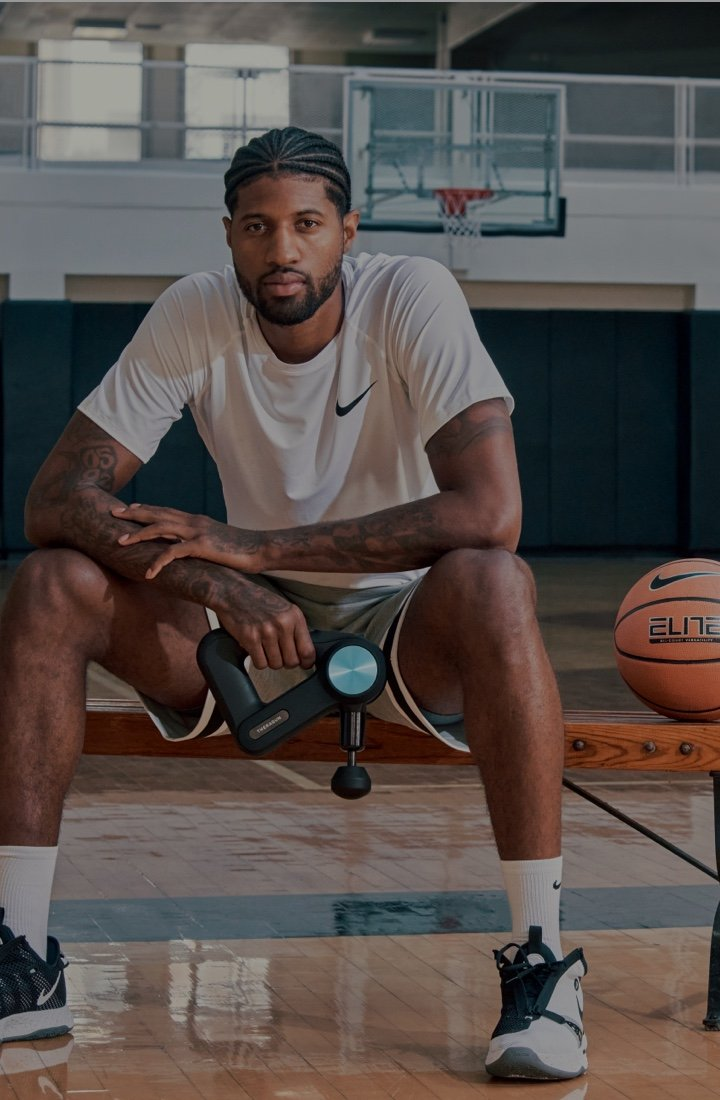 Paul George holding a Theragun PRO