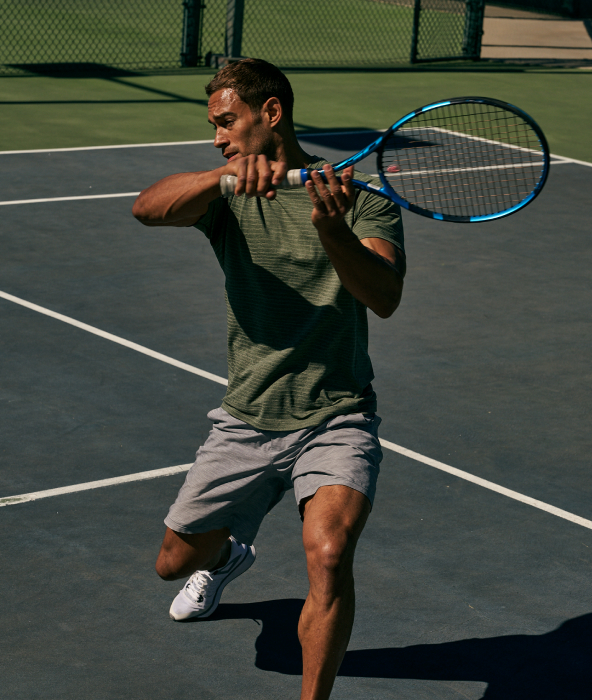 man swinging tennis racket