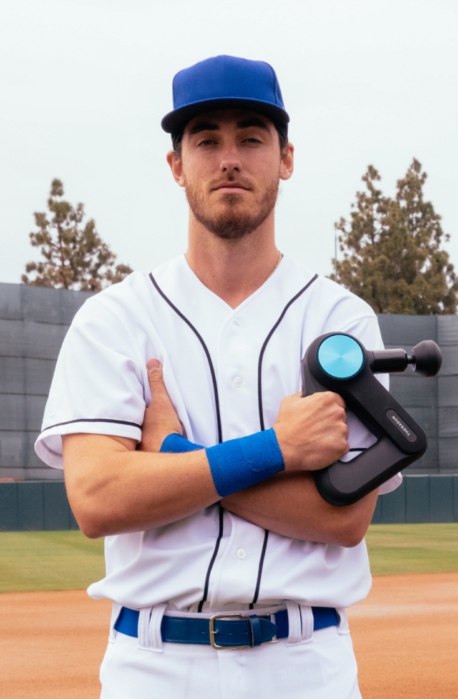 Cody Bellinger holding a Theragun PRO device