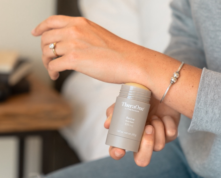 woman using TheraOne Revive Balm Stick on wrist