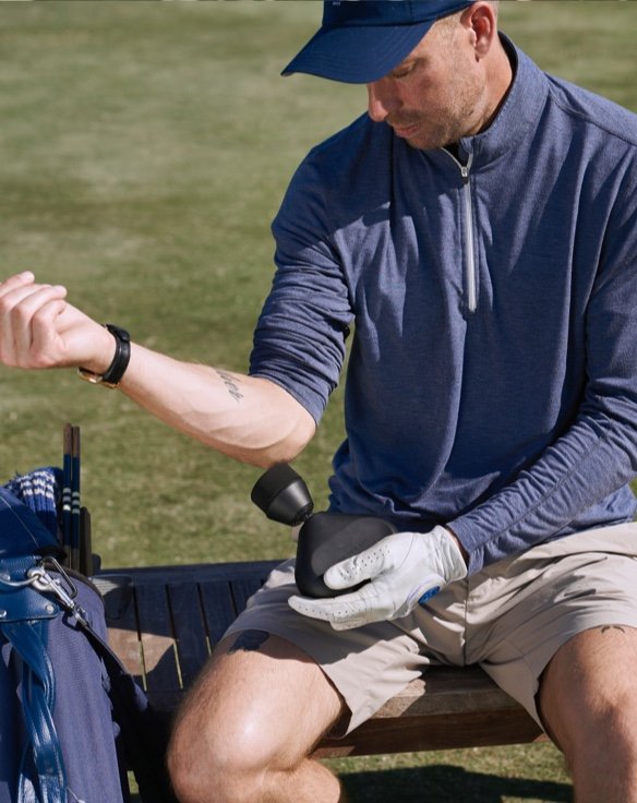 man treating shoulder with device